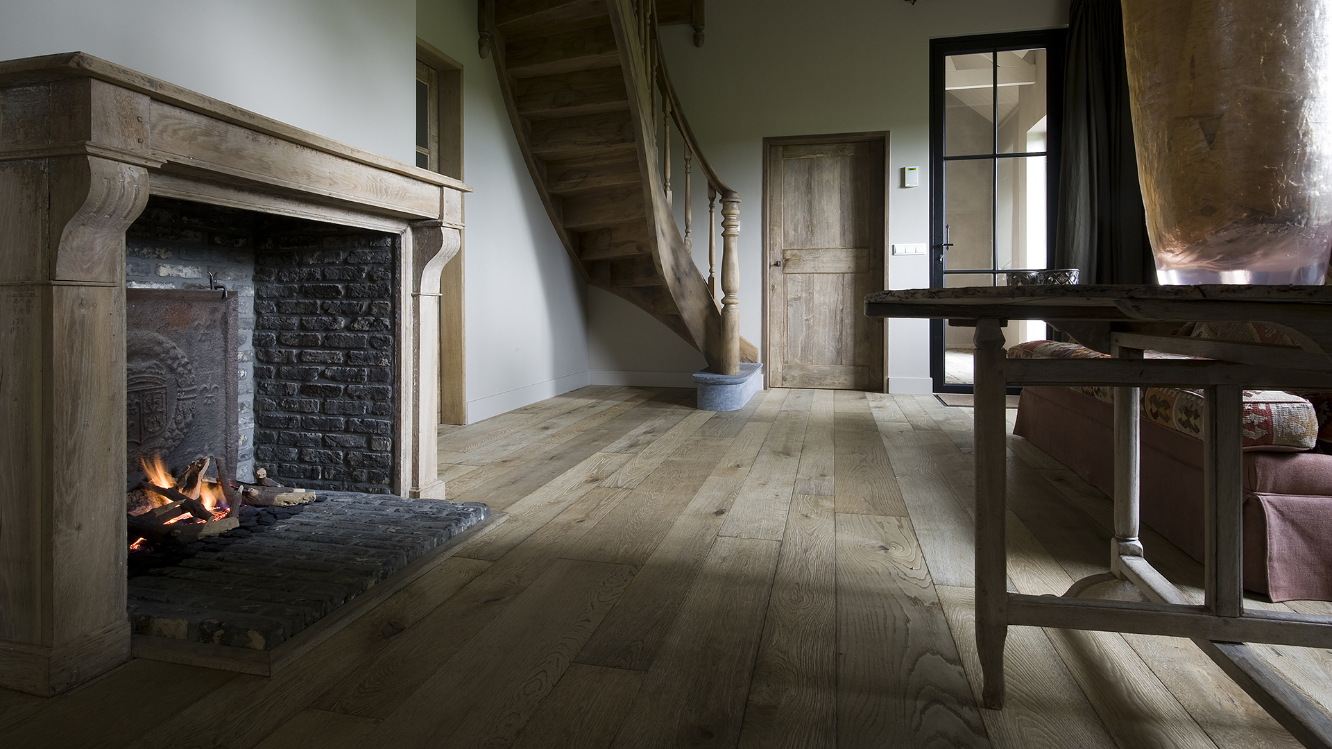 Magma Pacaya rustic floor in barn conversion with fireplace and curved staircase