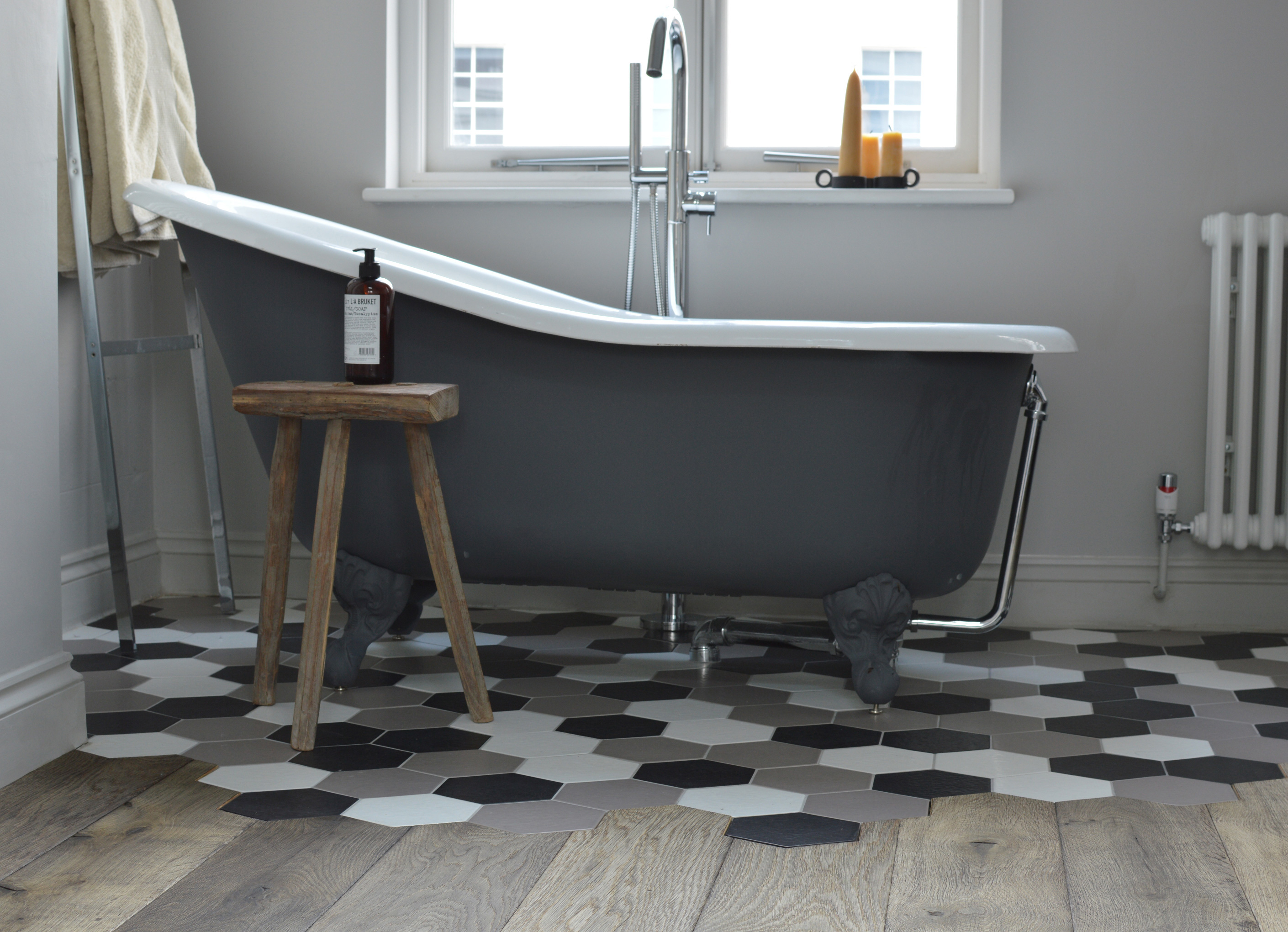 Oak magma stromboli plank meeting hexagon tiles with a free standing bath and wooden stool
