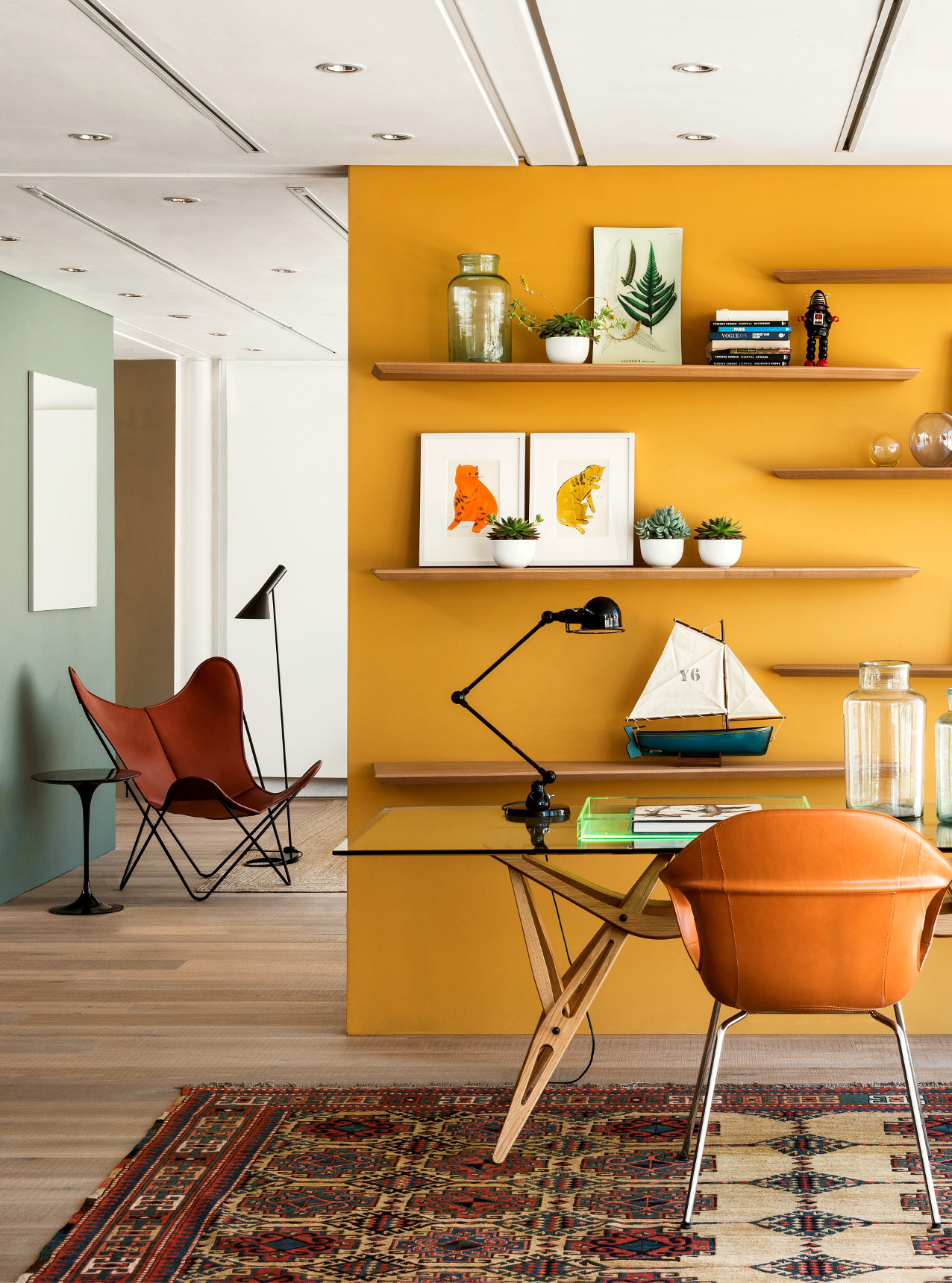 Oak tate skye plank in the conran store with open shelves on a yellow wall and a leather knoll butterfly chair