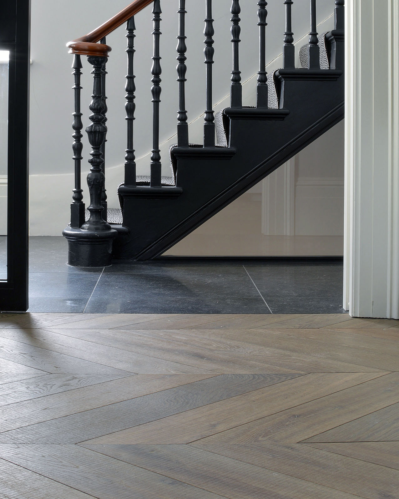 Oak tate tiree chevron against floor tiles and a staircase
