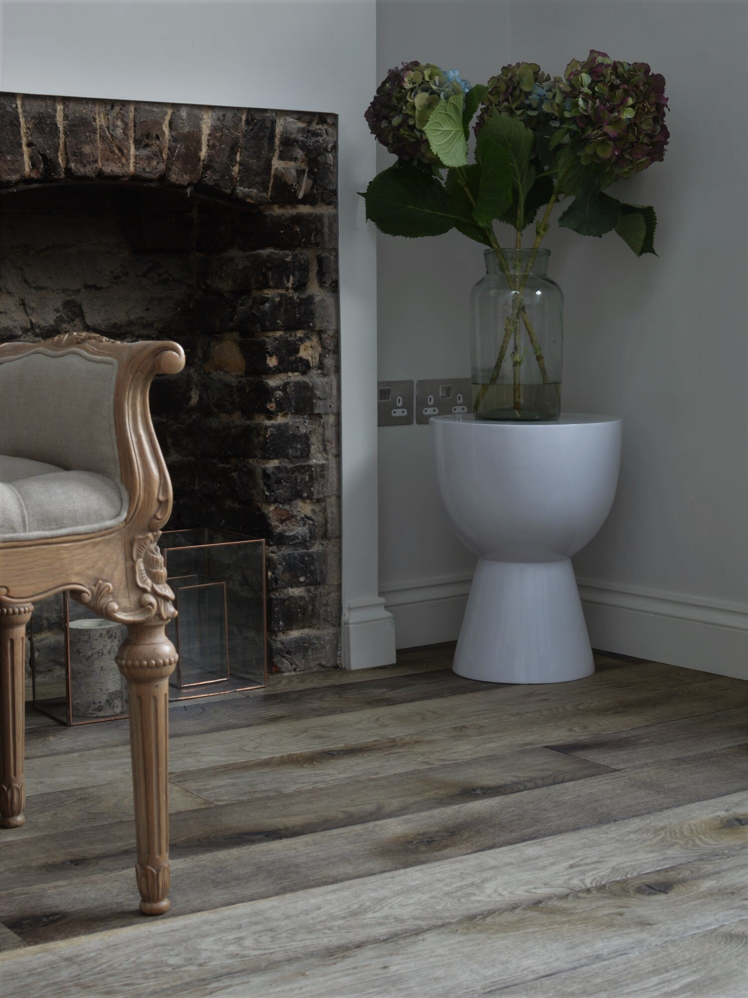 Oak Stromboli with fireplaceand white stool in the corner