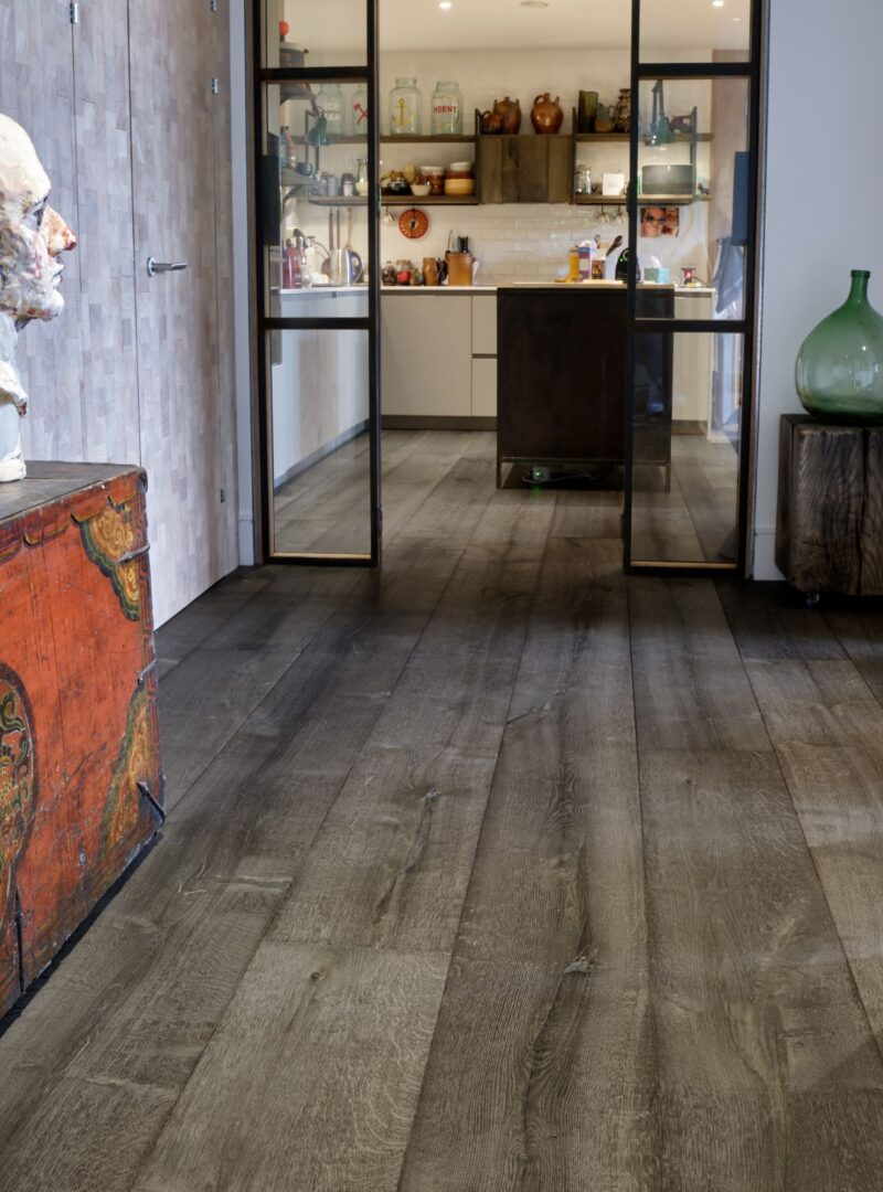 Magma mayon dark textured oak engineered flooring in hallway with kitchen in background and steel doors
