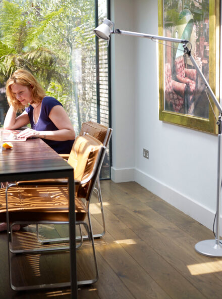 Oak Strata palisades plank with lady sitting at dining table with leather chairs and french doors to garden