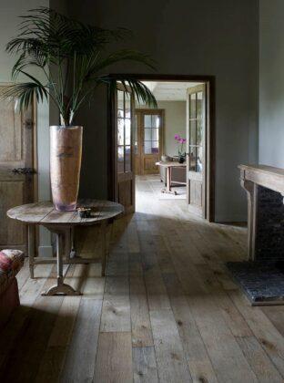 Magma Pacaya rustic floor in barn conversion with fireplace and palm