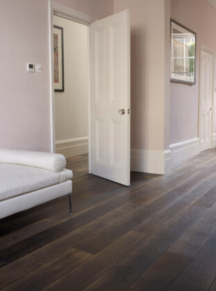 Oak Landmark Killerton plank dark brown floor with pink walls and white daybed.