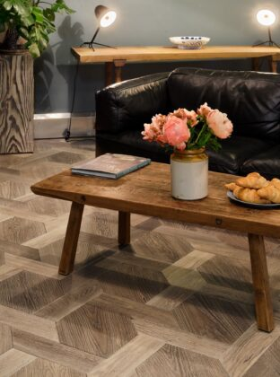 Oak landmark scotney in mansionweave pattern with coffee table and black sofa in solid floor showroom shoreditch