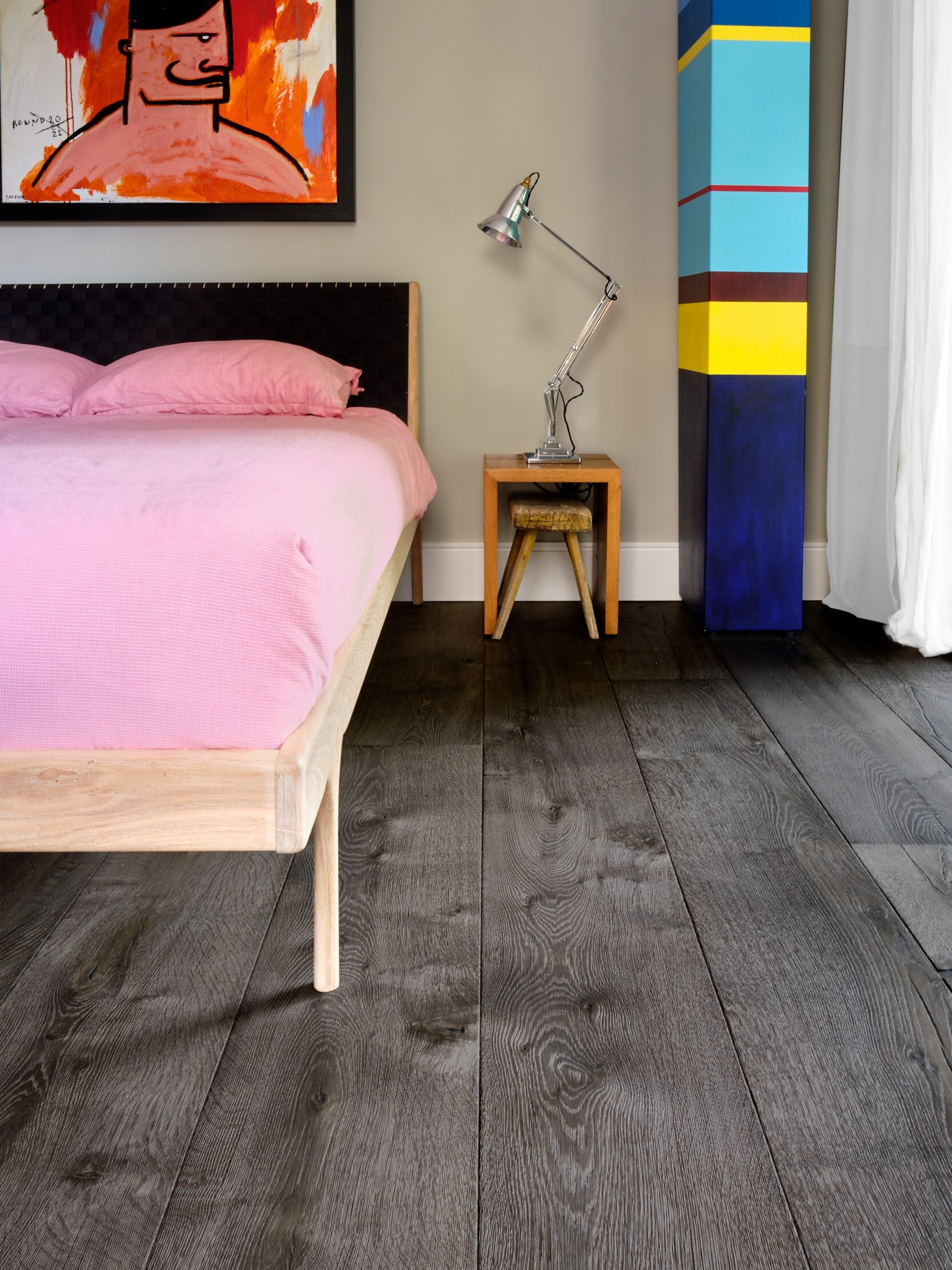 Magma mayon dark textured oak engineered floor in bedroom with colourful art and anglepoise lamp