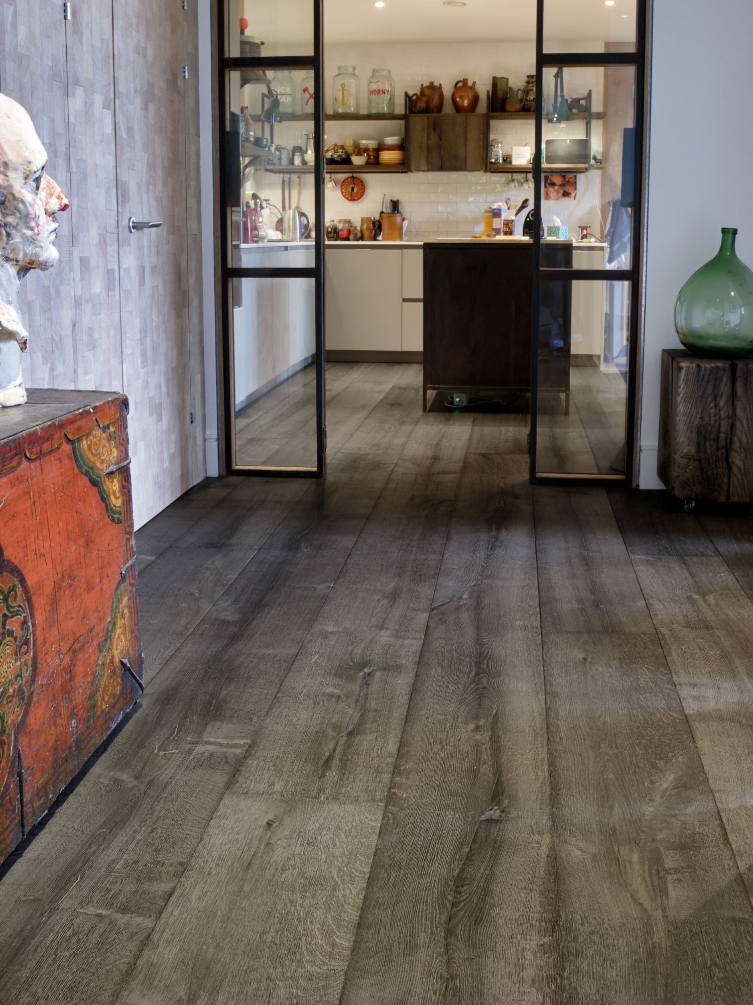 Magma mayon dark textured oak engineered flooring in hallway with kitchen in background and steel doors