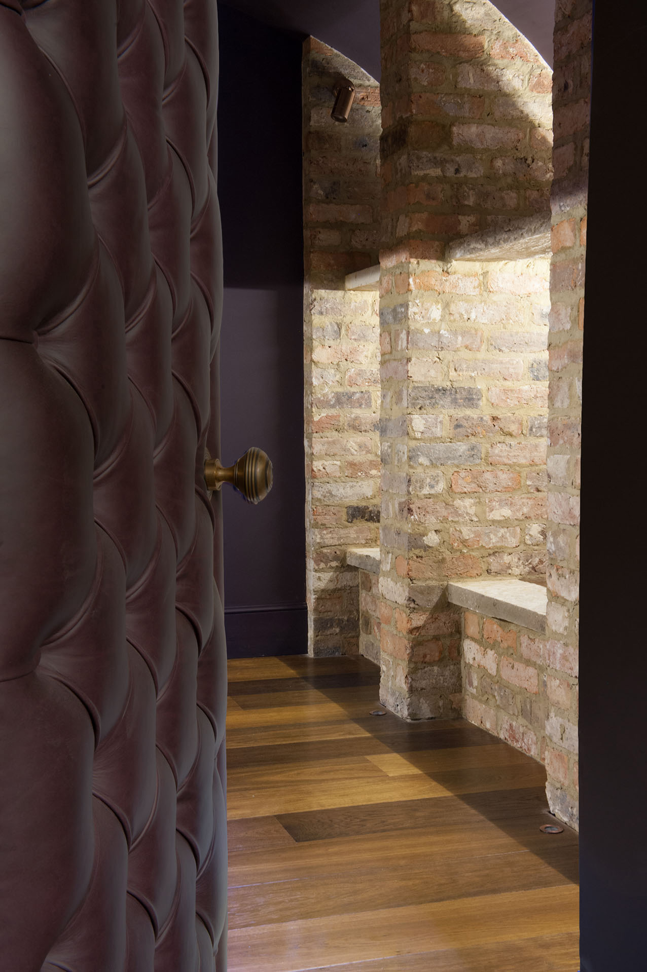 Oak landmark tatton plank in cellar with padded door and brick walls