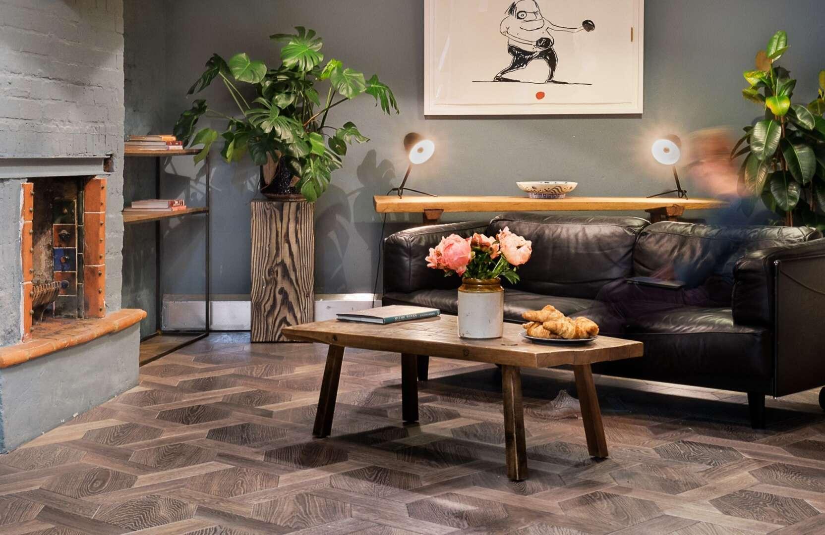 Solid floor london snug in showroom with fireplace black leather sofa on mansion weave oak flooring