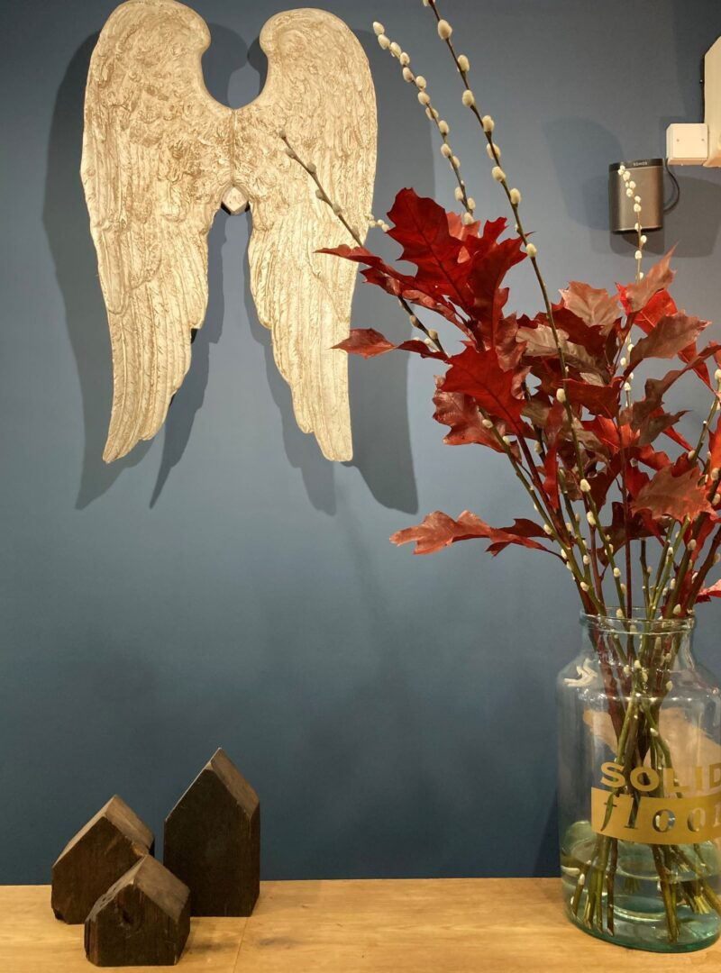 Red oak leaves in solid floor jar against blue wall with angel wings and timber houses