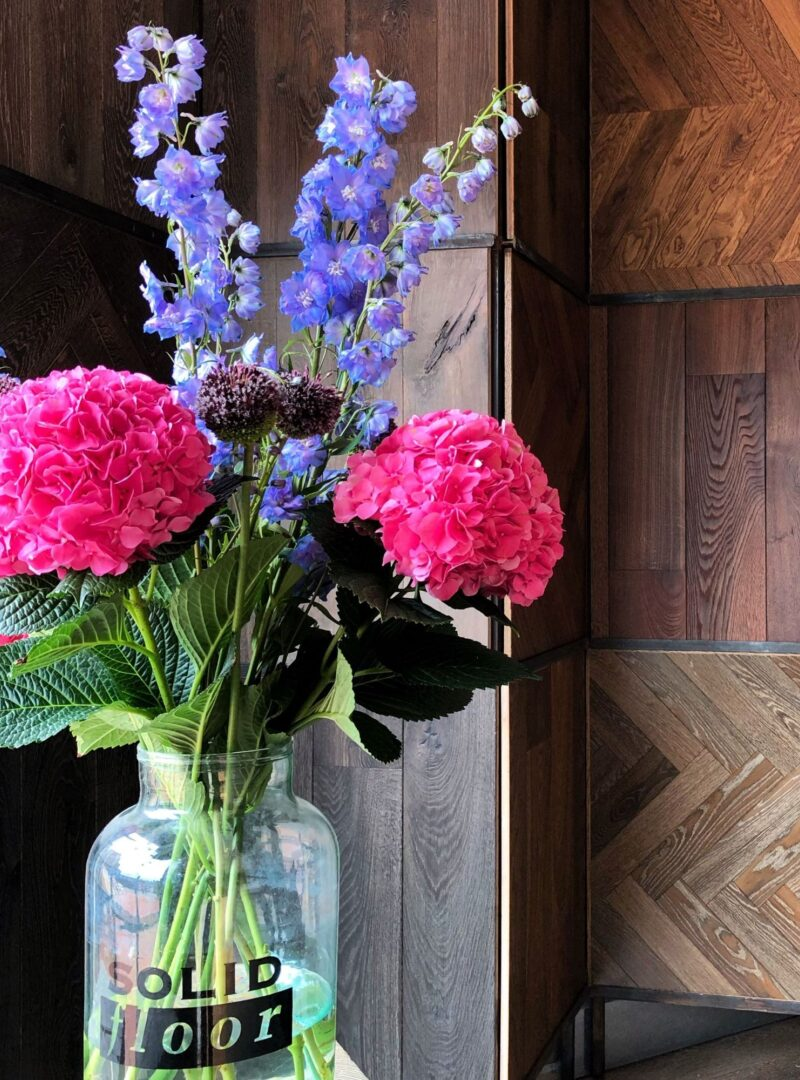 Timber flooring sample panels with flowers in solid floor jar