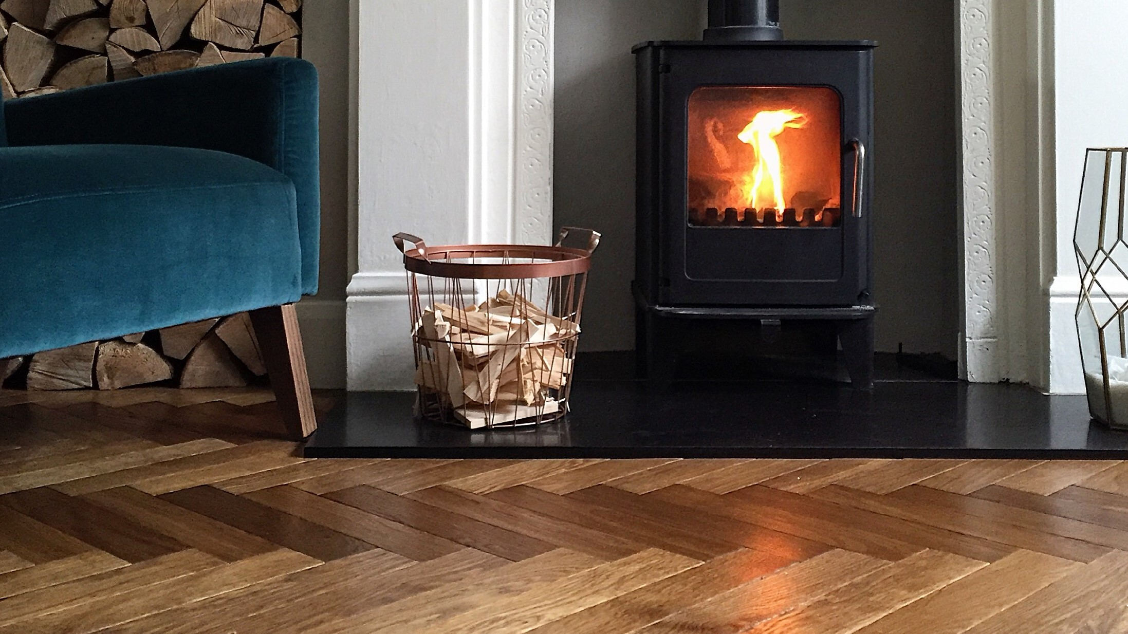 Landmark Dalton herringbone floor with blue velvet chair and wood burner